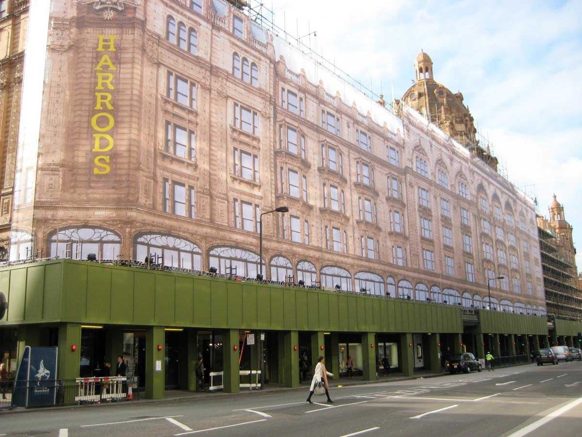 Harrods store front covered in green hoarding